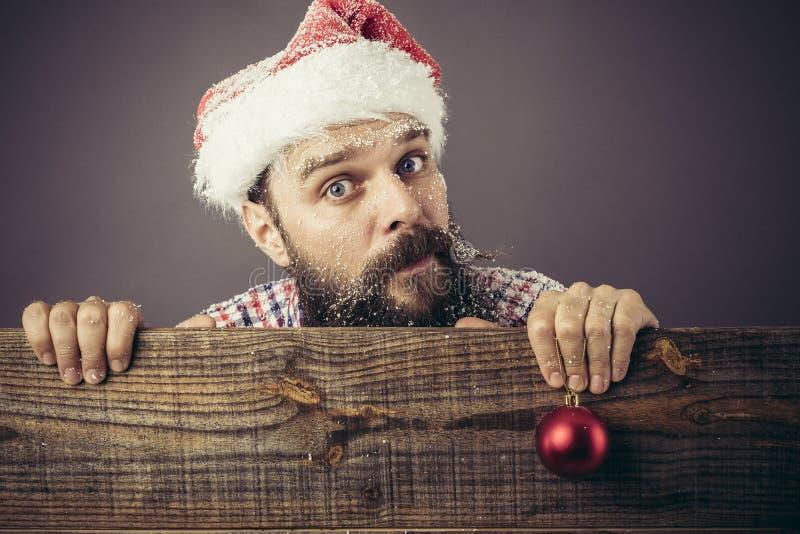 Portret van een grappige gebaarde mens die met santa GLB een rode rou houden royalty-vrije stock afbeeldingen