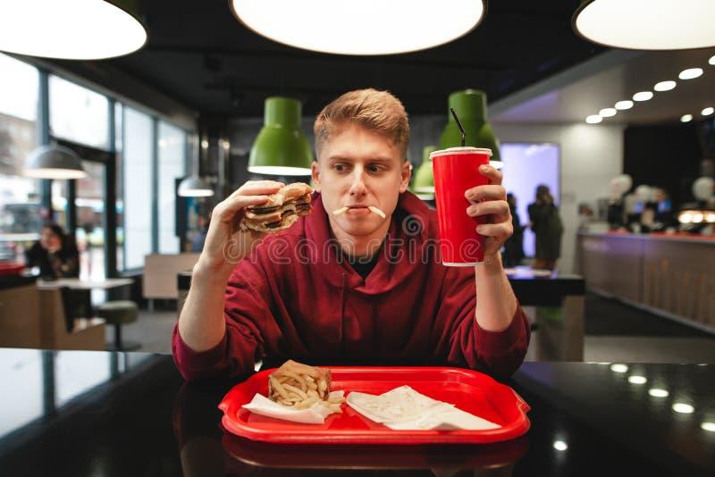 Portret van een grappige jonge mens die snel voedsel eten bij de achtergrond van het restaurant stock afbeelding