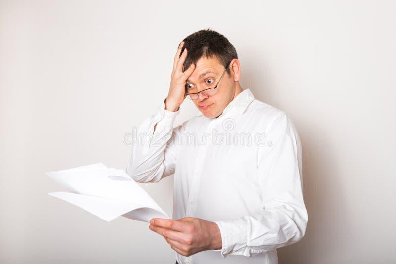Portret van een grappige kaukasische zakenman, geschokt door een open bril voor een financieel rapport, slecht nieuwsconcept stock foto