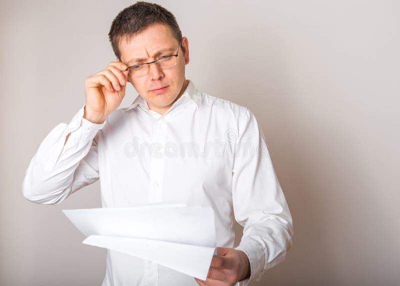 Portret van een grappige kaukasische zakenman, geschokt door een open bril voor een financieel rapport, slecht nieuwsconcept stock fotografie