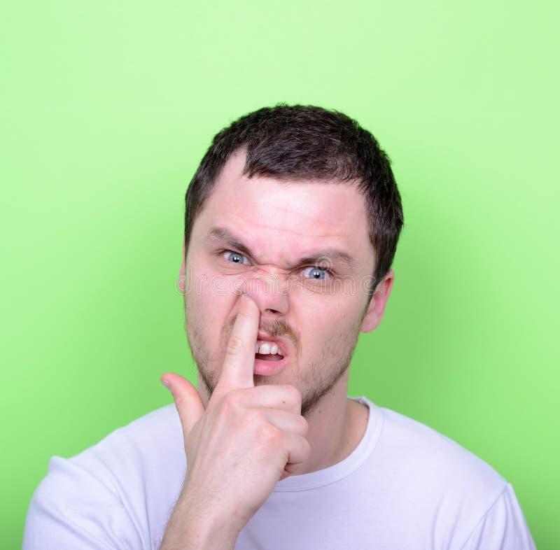 Portret van een grappige kerel met vinger in zijn neus tegen groene bedelaars royalty-vrije stock foto's