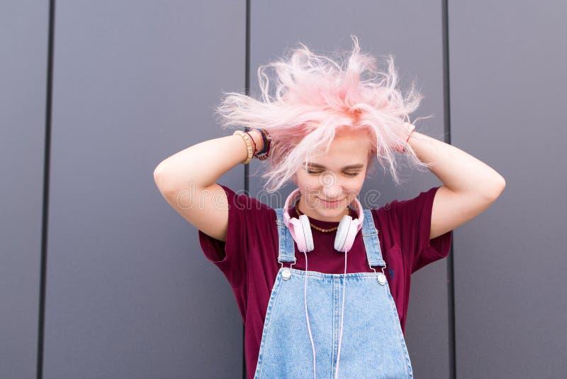 Portret van een helder, positief meisje met roze haar, modieuze de jeugdkleding en hoofdtelefoons stock foto's