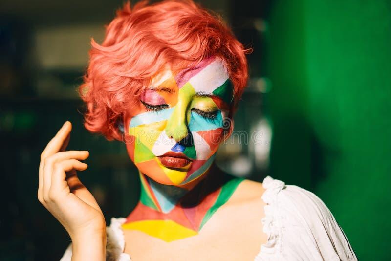 Portret van een heldere vrouw met oranje haar en veelkleurige make-up stock afbeeldingen