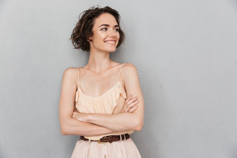 Portret van een het glimlachen jonge vrouw status stock afbeeldingen