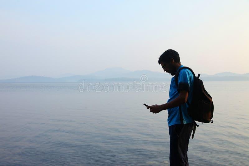 Portret van een het glimlachen kerel die telefoon met behulp van Jonge mens die op smartphone bij zonsondergang dichtbij een meer stock foto's