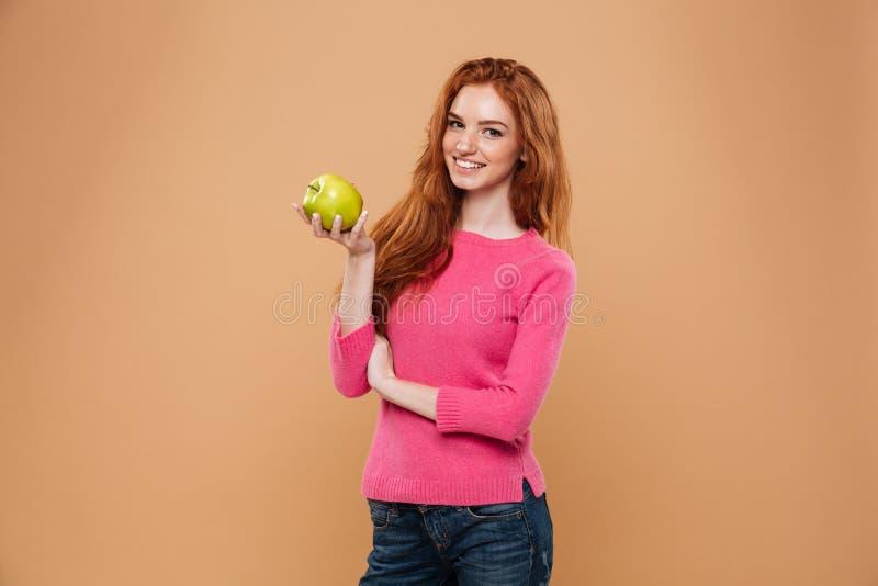 Portret van een het glimlachen mooie de holdingsappel van het roodharigemeisje royalty-vrije stock foto's