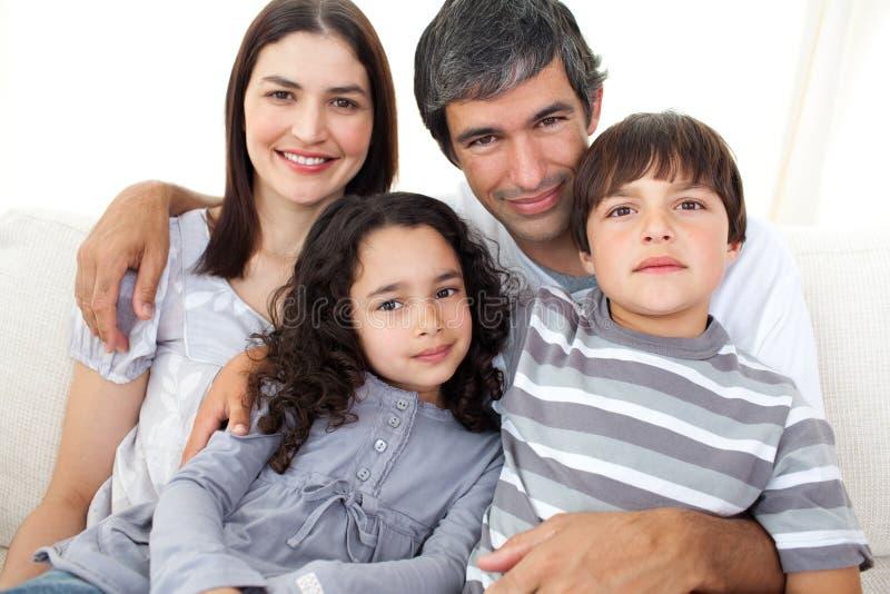 Portret van een het houden van familiezitting op een bank royalty-vrije stock foto's