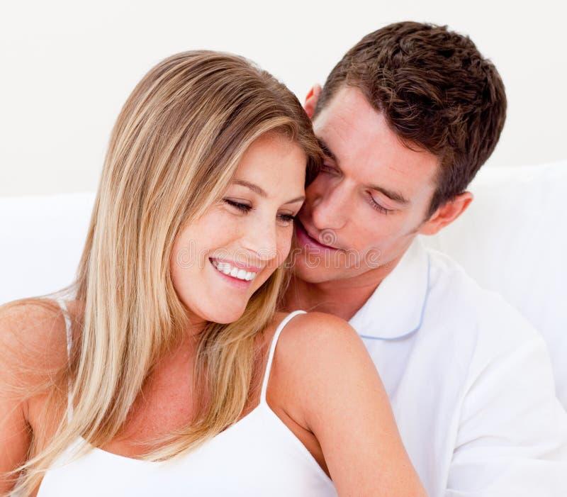 Portret van een het houden van paarzitting op bed stock foto