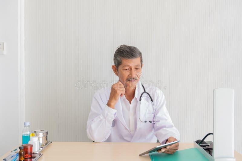 Portret van een hogere medische informatie van de artsencontrole over de tablet royalty-vrije stock fotografie