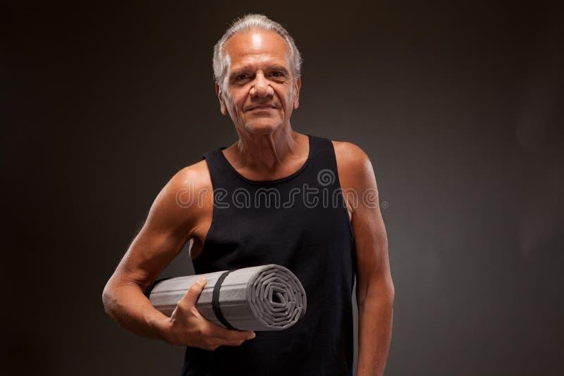 Portret van een hogere mens met een yogamat stock afbeeldingen