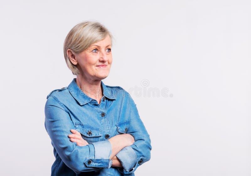 Portret van een hogere vrouw in studio, gekruiste wapens stock fotografie