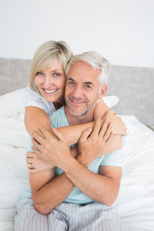 Portret van een houdend van rijp paar in bed stock foto's