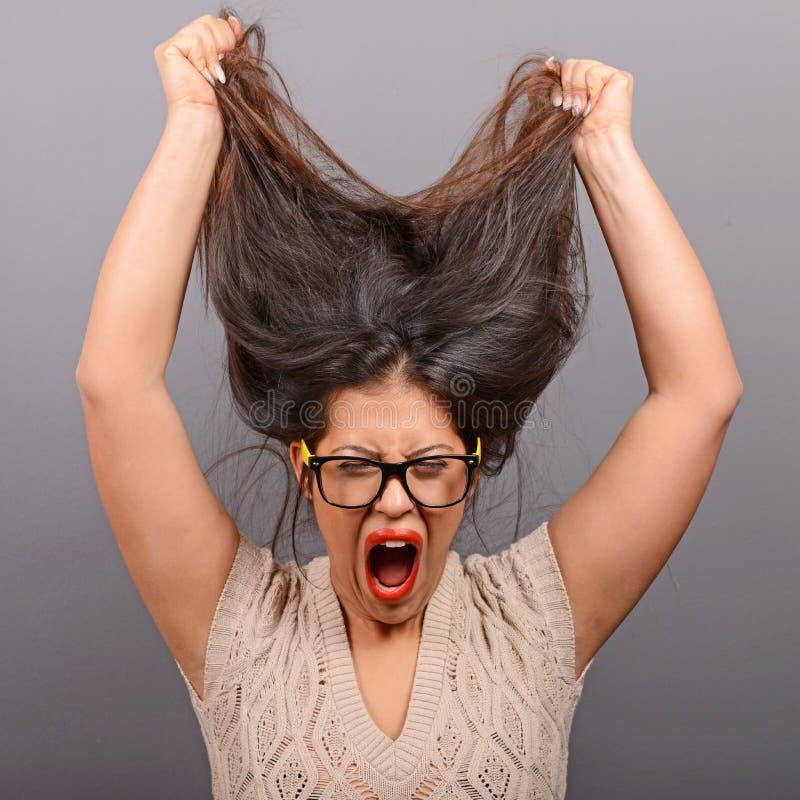 Portret van een hysterische vrouw die haar trekken uit tegen grijze achtergrond stock foto