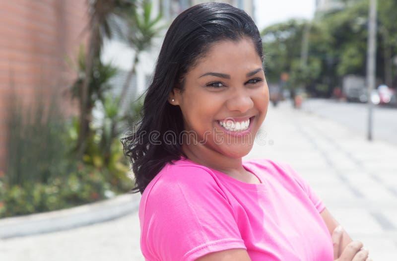 Portret van een inheemse Latijnse vrouw in een roze overhemd in stad stock afbeelding