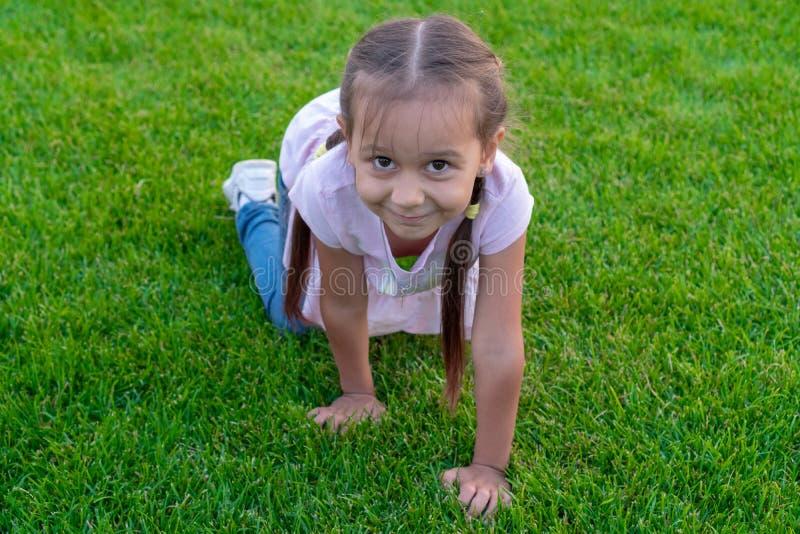 Portret van een 5 jaar oud meisje die in het groene gras in het park hurken en op een zonnige dag glimlachen De ruimte van het ex royalty-vrije stock foto