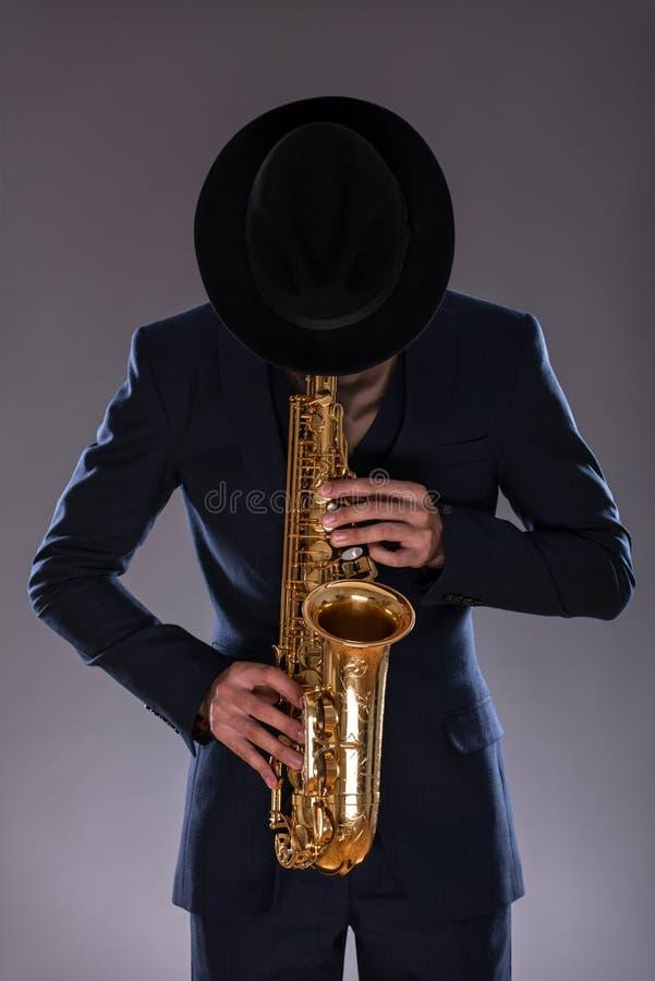 Portret van een jazzmens in een kostuum met hoed het verbergen royalty-vrije stock fotografie