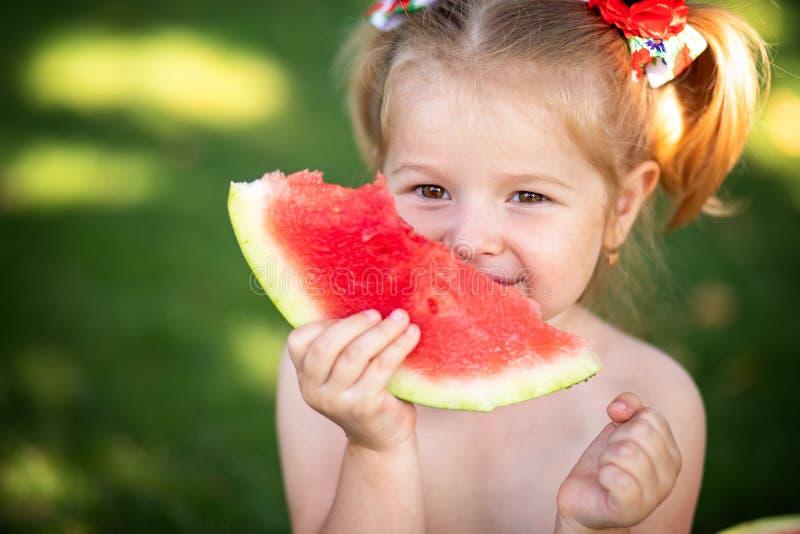 Portret van een jong blondemeisje met watermeloen, de zomer openlucht royalty-vrije stock foto