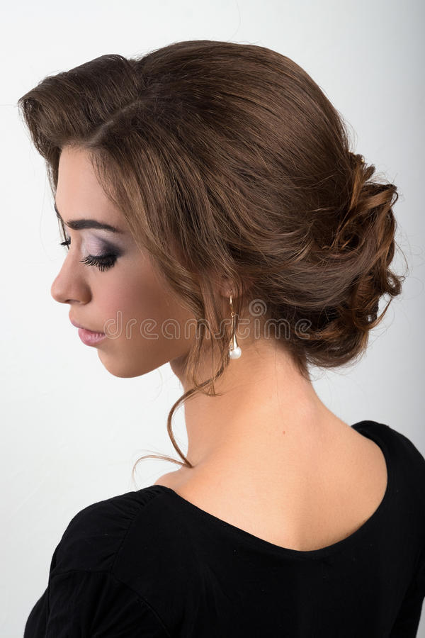 Portret van een jong brunette met verzamelde gelijk makende haar en make-up, meningsprofiel stock fotografie