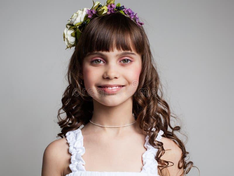 Portret van een jong donkerbruin meisje in een bloemkroon stock foto's