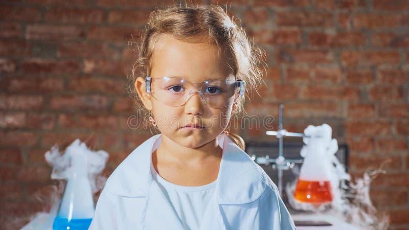 Portret van een jong ernstig meisje van het wetenschapperkind in een chemielaboratorium royalty-vrije stock foto