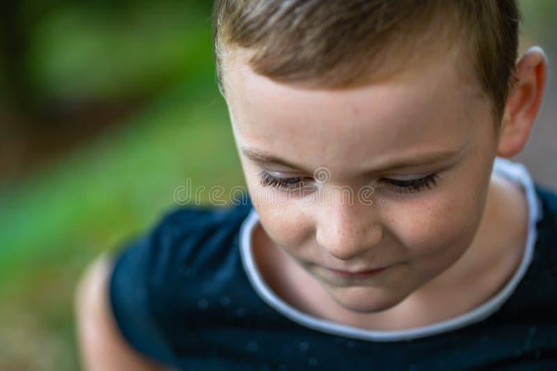 Portret van een Jong geitje in een Park, Nadenkend Vangen - kijk op van hem stock foto