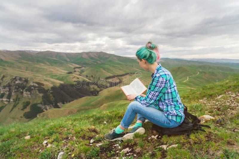 Portret van een jong hipstermeisje met multi-colored haarzitting op aard in de bergen die een boek lezen Het concept royalty-vrije stock fotografie