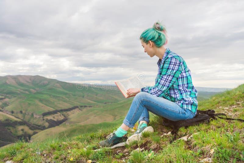Portret van een jong hipstermeisje met multi-colored haarzitting op aard in de bergen die een boek lezen Het concept stock foto's