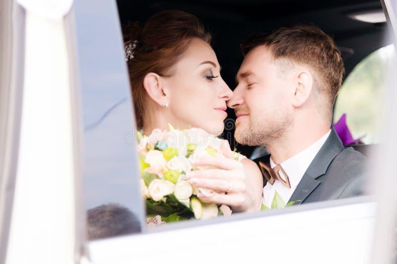 Portret van een jong kussend paar in liefde met een jonggehuwdepaar naast een boeket in het venster van een huwelijksauto royalty-vrije stock foto