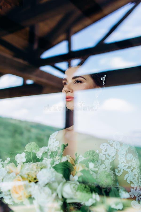 Portret van een jong meisje van de bruid met professionele huwelijksmake-up en kapsel in venster stock afbeeldingen