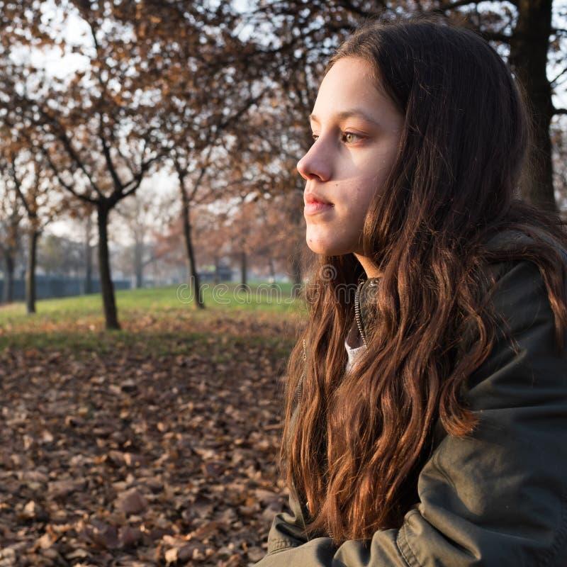 Portret van een jong meisje die met lang haar, bij het park zitten, die ver weg het dagdromen staren stock foto's