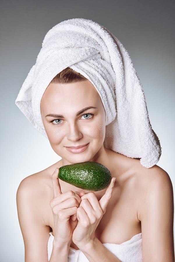 Portret van een jong meisje met gezonde en zijdeachtige huid, met een witte handdoek op haar hoofdholding een avocadoplak met een royalty-vrije stock fotografie