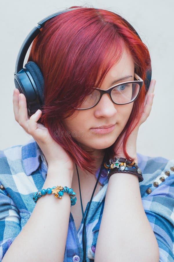Portret van een jong meisje met hoofdtelefoons stock foto's