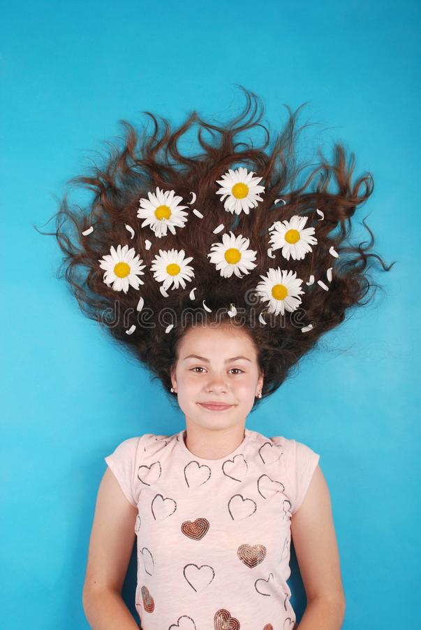 Portret van een jong meisje met madeliefjes in hun haar die op de vloer liggen royalty-vrije stock foto