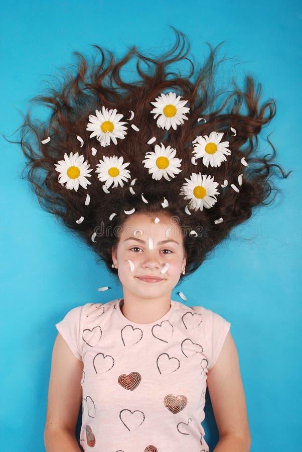 Portret van een jong meisje met madeliefjes in hun haar die op de vloer liggen stock afbeeldingen