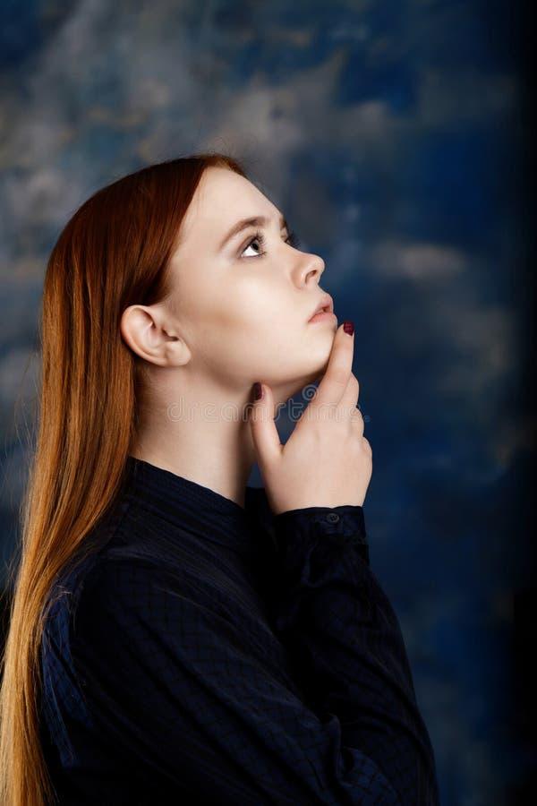 Portret van een jong meisje op donkere vage achtergrond stock fotografie
