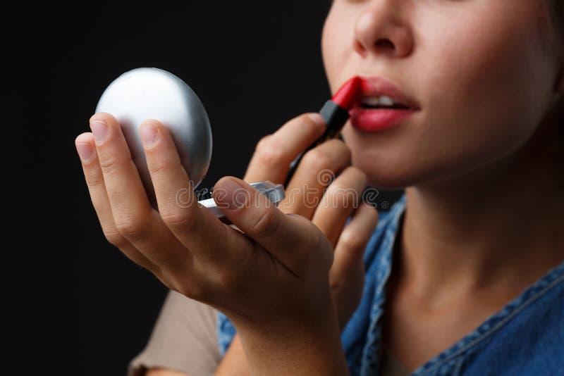 Portret van een jong meisje op een zwarte achtergrond die haar lippen met rode lippenstift schildert royalty-vrije stock afbeeldingen