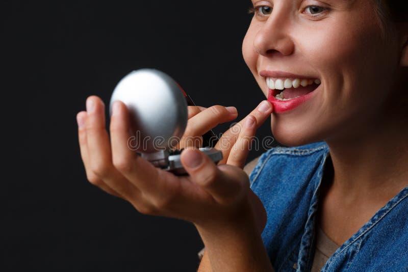 Portret van een jong meisje op een zwarte achtergrond die haar lippen met rode lippenstift schildert royalty-vrije stock foto's