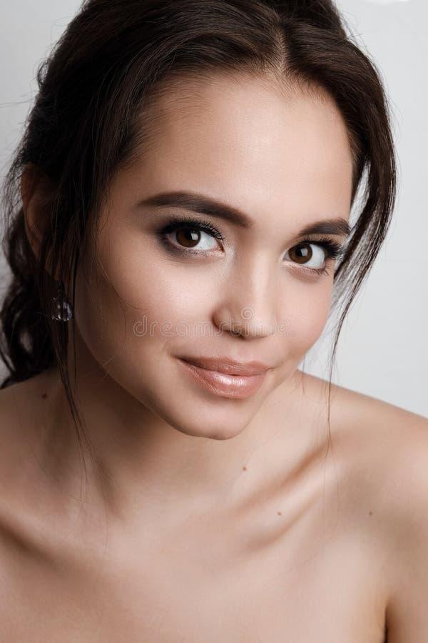 Portret van een jong meisjesbrunette met bruine ogen en zachte natuurlijke make-up Meisje dat en de camera glimlacht bekijkt stock afbeelding