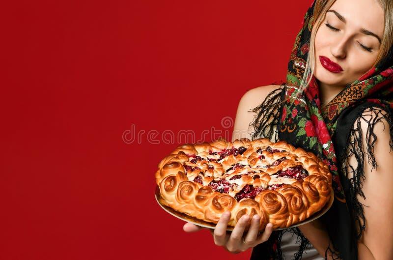 Portret van een jong mooi blonde in headscarf die een heerlijke eigengemaakte bessenpastei houden stock afbeelding