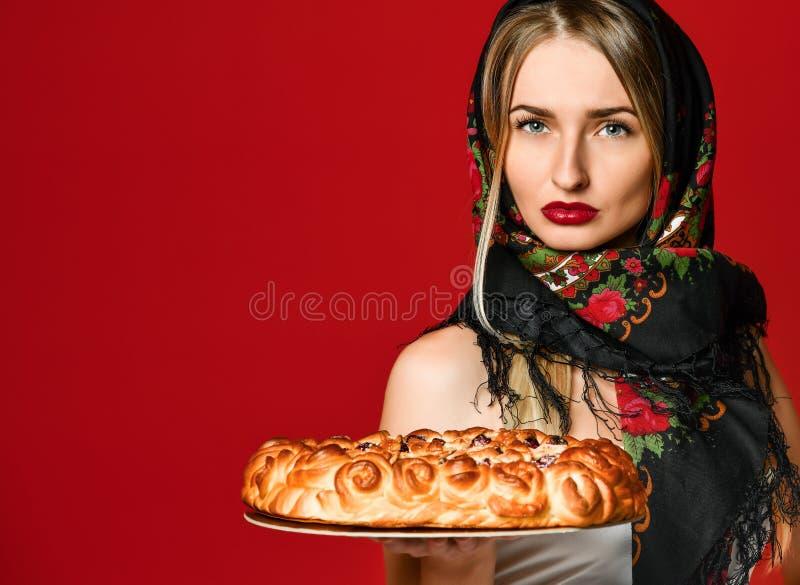Portret van een jong mooi blonde in headscarf die een heerlijke eigengemaakte kersenpastei houden royalty-vrije stock fotografie
