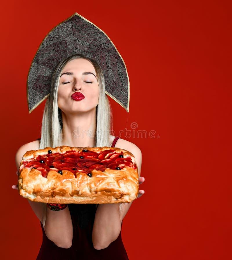 Portret van een jong mooi blonde in headscarf die een heerlijke eigengemaakte kersenpastei houden royalty-vrije stock afbeeldingen