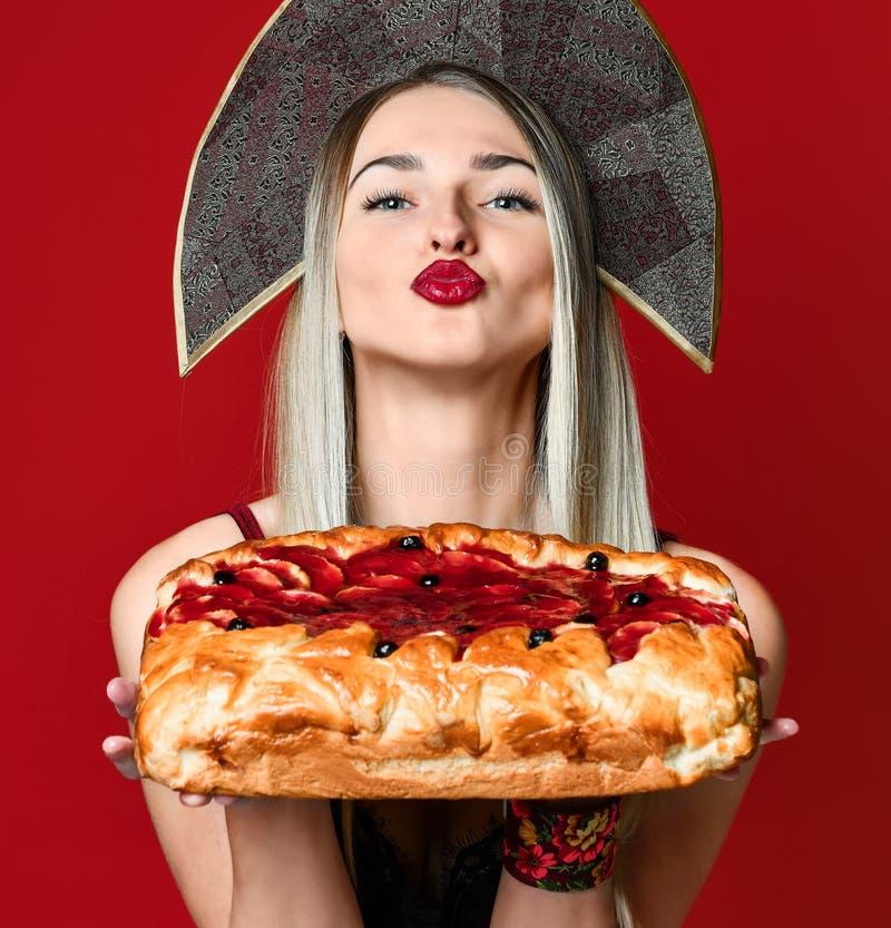 Portret van een jong mooi blonde in kokoshnik die een heerlijke eigengemaakte kersenpastei houden stock foto