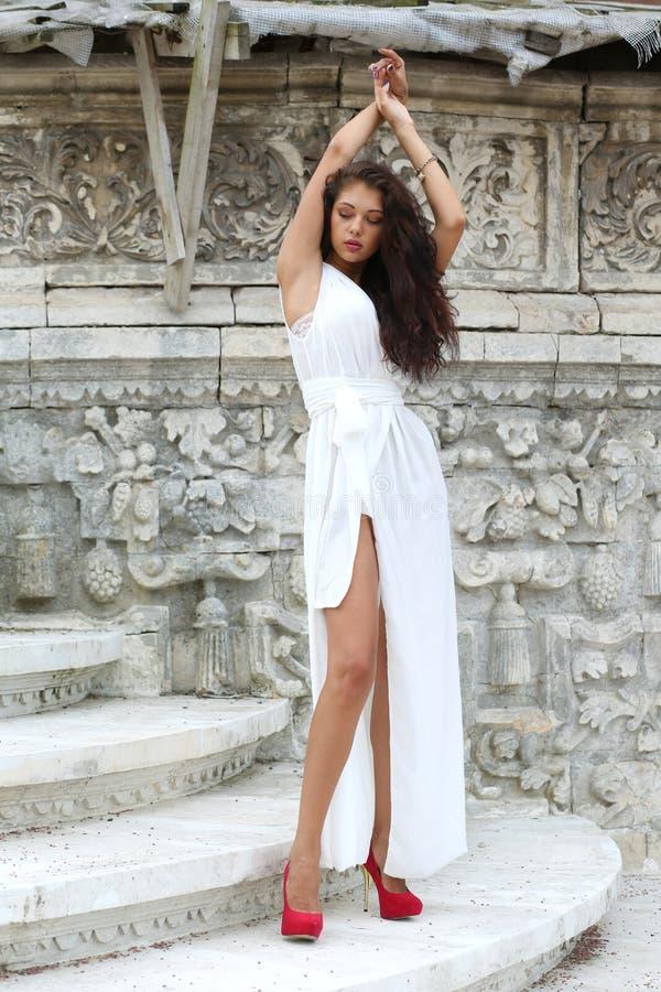 Portret van een jong mooi brunette in een lange witte kleding stock afbeelding