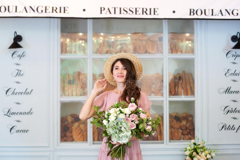 Portret van een jong mooi gelukkig meisje die een roze kleding, strohoed dragen, houdend een boeket die van bloemen, in de straat royalty-vrije stock foto