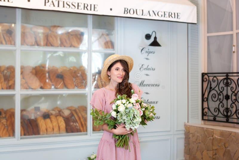 Portret van een jong mooi gelukkig meisje die een roze kleding, strohoed dragen, houdend een boeket die van bloemen, in de straat royalty-vrije stock afbeeldingen