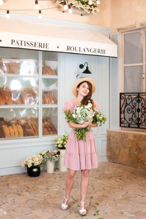 Portret van een jong mooi gelukkig meisje die een roze kleding, strohoed dragen, houdend een boeket die van bloemen, in de straat stock afbeeldingen