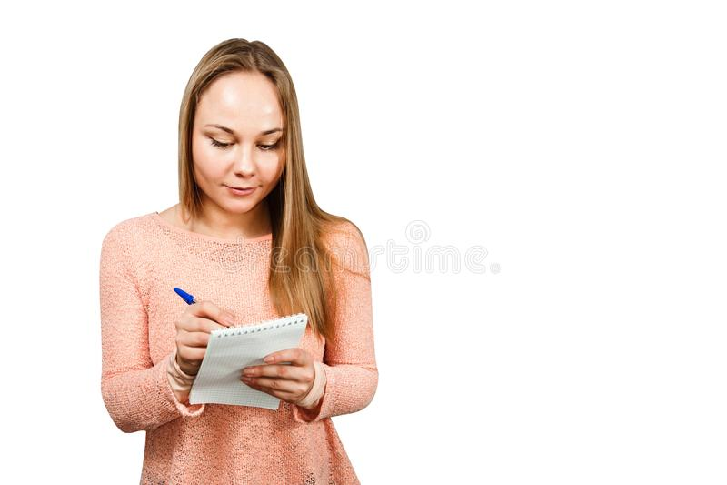 Portret van een jong mooi meisje dat in een notitieboekje schrijft Ge?soleerdj op witte achtergrond royalty-vrije stock fotografie