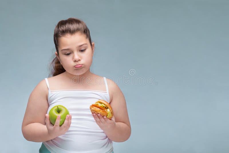 Portret van een jong mooi meisje die rood Apple in ??n hand en een hamburger in andere op een witte achtergrond houden Waar stock afbeeldingen