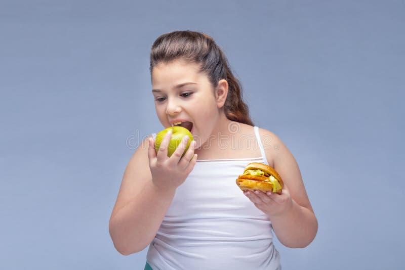 Portret van een jong mooi meisje die rood Apple in ??n hand en een hamburger in andere op een witte achtergrond houden Waar stock foto's