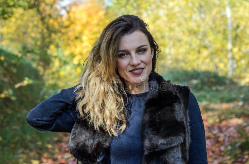 Portret van een jong mooi meisje met lang haar in een bontjas tijdens een gang in het de herfstpark royalty-vrije stock foto